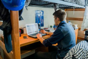 student typing on laptop in dorm room